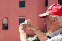 Homem superior que toma fotos com câmera compacta Fotos de Stock Royalty Free