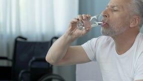 Homem superior que toma o comprimido, cadeira de rodas que está no fundo, curso da reabilitação video estoque