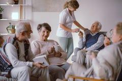 Homem superior que toma um copo do chá de seu cuidador no lar de idosos imagens de stock royalty free