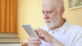 Homem superior que usa a aplicação para aprender línguas estrangeiras no smartphone, fazendo o treinamento em-app video estoque