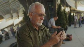 Homem superior que usa o ar livre do smartphone no terminal de aeroporto vídeos de arquivo