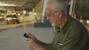 Homem superior que usa o ar livre do smartphone no terminal de aeroporto filme