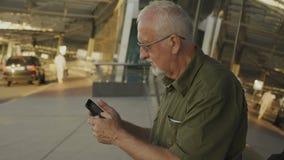 Homem superior que usa o smartphone fora vídeos de arquivo