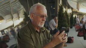 Homem superior que usa o smartphone fora filme
