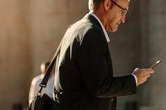 Homem superior que usa o telefone celular ao andar na rua ao escritório fotografia de stock royalty free