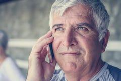 Homem superior que usa o telefone esperto no gym Homem que fala no phon imagens de stock royalty free