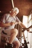 Homem superior que usa o telefone esperto no gym Mensagens de datilografia do homem sobre foto de stock