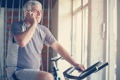 Homem superior que usa o telefone esperto no gym Homem que senta-se em elíptico fotos de stock royalty free