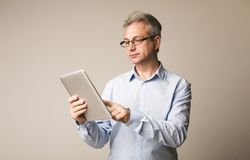 Homem superior que usa a tabuleta digital, Internet surfando fotografia de stock