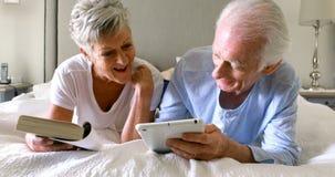 Homem superior que usa a tabuleta digital quando mulher que lê um livro na cama vídeos de arquivo