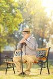 Homem superior triste com um bastão que senta-se no banco em um parque Imagens de Stock Royalty Free