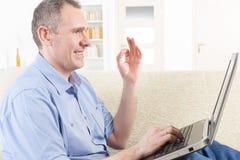 Homem surdo que usa a linguagem gestual com portátil imagens de stock royalty free