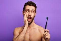 Homem surpreendido com a palma em seu mordente que guarda uma escova de dentes imagem de stock