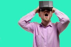Homem surpreendido com vidros da realidade virtual na camisa lilás foto de stock