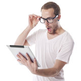 Homem surpreendido do lerdo que olha o computador da tabuleta Fotos de Stock