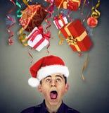 Homem surpreendido no chapéu de Papai Noel que olha acima em presentes do Natal Imagem de Stock