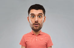 Homem surpreendido no t-shirt do polo sobre o fundo cinzento Imagem de Stock