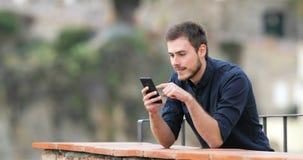 Homem surpreendido que encontra o índice em um telefone esperto video estoque