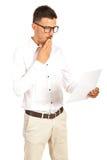 Homem surpreendido que lê um papel Imagem de Stock Royalty Free