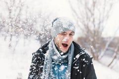 Homem surpreendido que sente flocos de neve frios em sua cara durante uma neve fotos de stock royalty free