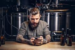 Homem Tattooed do moderno com barba à moda e cabelo usando o smartphone ao sentar-se no contador da barra na cervejaria indie imagens de stock