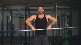 Homem tattooed farpado forte em um gym do crossfit que levanta um barbell video estoque