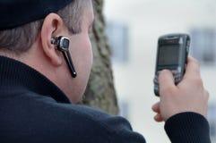 Homem Texting & fone de ouvido sem fio desgastando Fotos de Stock Royalty Free