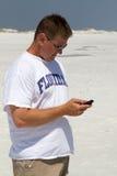 Homem Texting na praia foto de stock royalty free