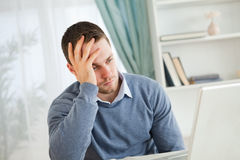 Homem Tired em seu portátil Foto de Stock Royalty Free