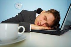 Homem Tired que dorme em um caderno Imagens de Stock