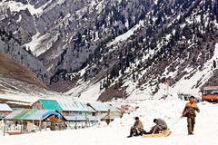Homem três com waitng do trenó o homem do turista um que sledding na neve, Jammu e Caxemira, Índia - 4 de abril de 2012 Imagem de Stock