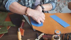Homem trabalhador novo que trabalha com couro usando-se crafting ferramentas filme