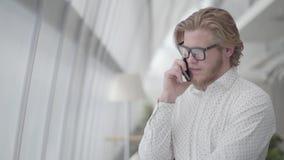Homem triste considerável nos vidros que estão em um escritório confortável claro que fala pelo telefone celular Homem de negócio video estoque