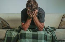 Homem triste e desesperado novo em casa que senta-se na cara da coberta do sofá do sofá com depressão das mãos e sentimento de so imagens de stock royalty free