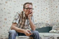 Homem triste e sério com o telecontrole em sua notícia da tevê do relógio da mão Fotos de Stock Royalty Free