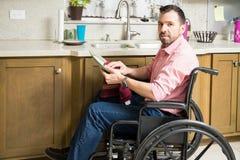 Homem triste em pratos de lavagem da cadeira de rodas fotos de stock royalty free