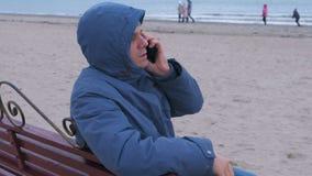 Homem triste em um azul abaixo do revestimento que senta-se em um banco na praia da areia, chamando o telefone celular e esperand filme