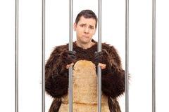 Homem triste em um traje do urso que está atrás das barras Fotografia de Stock Royalty Free