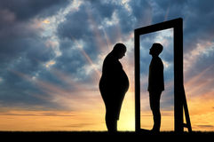 Homem triste gordo e sua reflexão no espelho de um homem normal contra o céu imagem de stock royalty free
