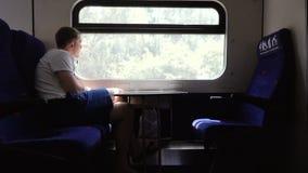 Homem triste nos fones de ouvido que olham para fora o trem da janela video estoque