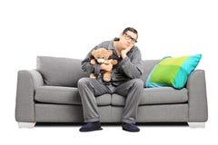 Homem triste nos pijamas que guardam um urso de peluche Fotografia de Stock Royalty Free