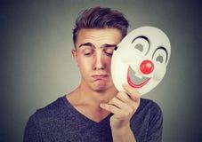 Homem triste novo que descola a máscara feliz do palhaço Emoções humanas fotos de stock