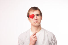 Homem triste que cobre seu olho com um coração Fotos de Stock Royalty Free