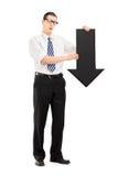Homem triste que guarda uma seta preta grande que aponta para baixo Fotografia de Stock Royalty Free