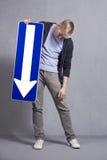 Homem triste que guardara o sinal da seta do sentido que aponta para baixo. Fotografia de Stock Royalty Free