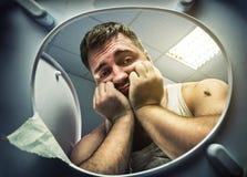 Homem triste que olha na bacia de toalete imagens de stock royalty free