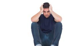 Homem triste que senta-se no assoalho ao guardarar sua cabeça Imagens de Stock Royalty Free