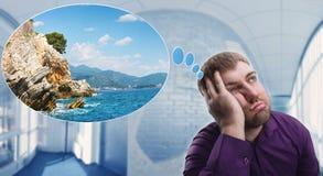 Homem triste que sonha sobre férias Foto de Stock Royalty Free