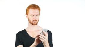 Homem vermelho novo do cabelo que guarda o smartphone móvel usando a mensagem texting dos sms do app Imagens de Stock Royalty Free