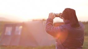 Homem, viajante, tomando a foto do nascer do sol no telefone esperto filme